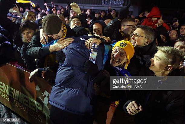 Paul Doswell manager of Sutton United is mobbed by fans as he celebrates winning The Emirates FA Cup Third Round Replay match between AFC Wimbledon...