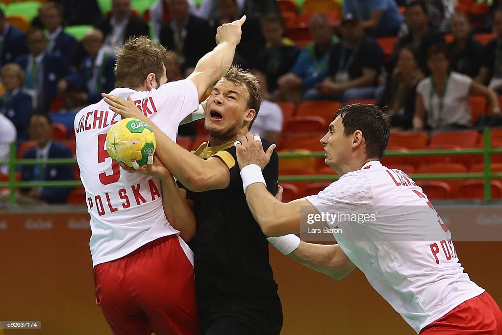 Paul Drux of Germany is blocked by Mateusz Jachlewski of Poland and Krzysztof Lijewski of Poland during the Men's Bronze Medal Match between Poland...