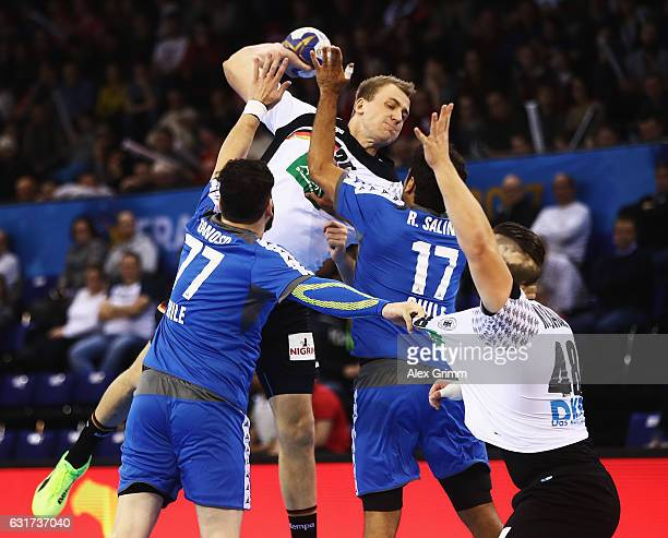 Paul Drux of Germany is challenged by Victor Donoso and Rodrigo Salinas of Chile during the 25th IHF Men's World Championship 2017 match between...