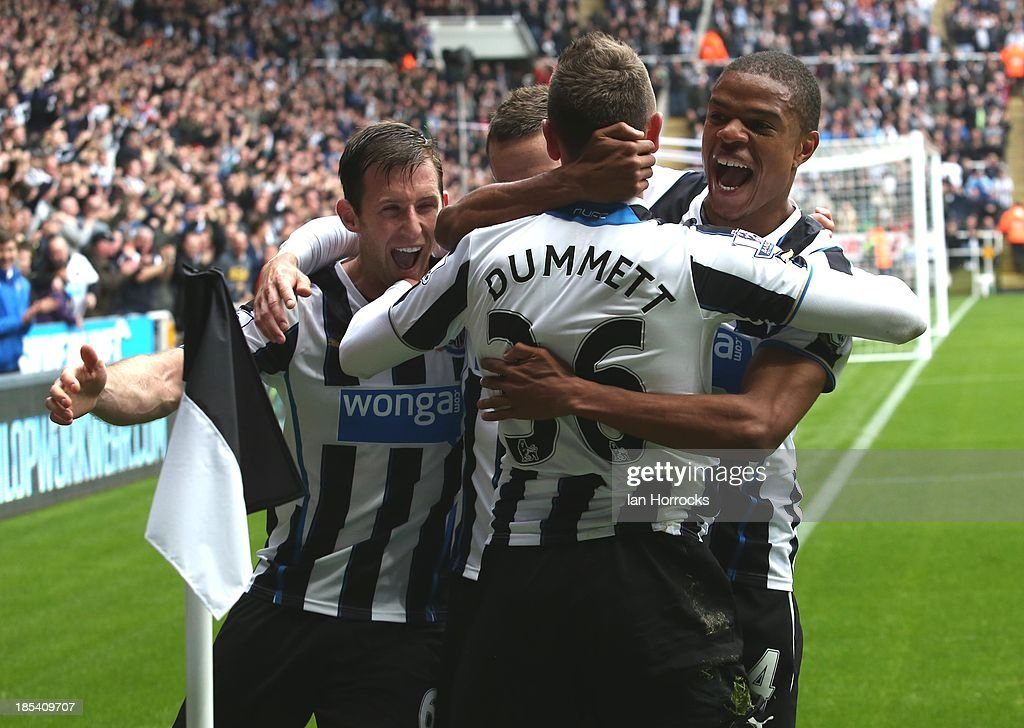 Paul Dummett of Newcastle United celebrates scoring the second Newcastle goal with Loic Remy (right) and Mike Williamson (left) during the Barclays Premier League game between Newcastle United and Liverpool at St James' Park on October 19, 2013 in Newcastle upon Tyne, England.