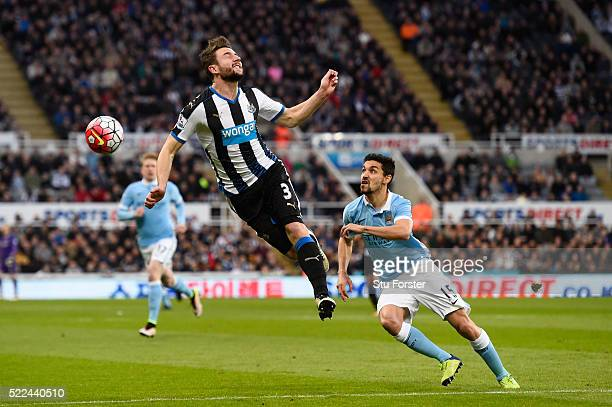 Paul Dummett of Newcastle United heads the ball clear of Jesus Navas of Manchester City during the Barclays Premier League match between Newcastle...