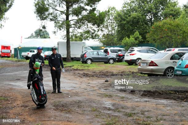 Paul Dunne of Ireland speaks with his caddie Darren Reynolds as he prepares to hit out of a car park on the 1st during day one of the Joburg Open at...