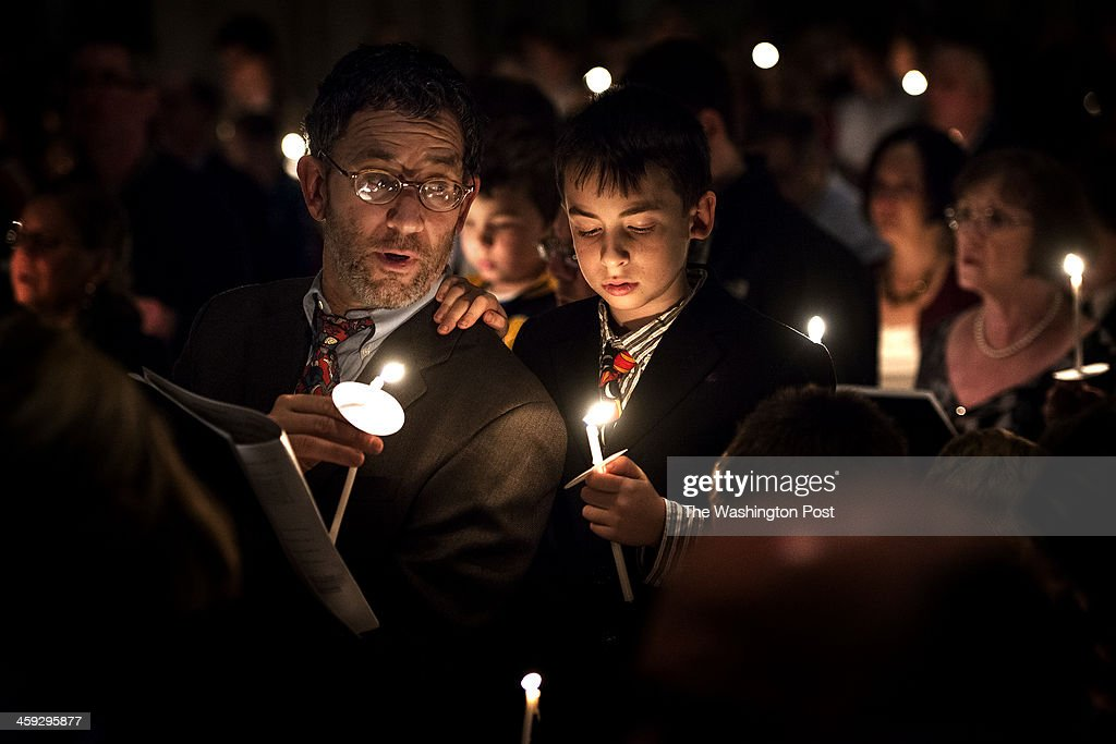 Paul Fagiolo of Takoma Park sings Silent Night with his son Anthony Fagiolo age 9 during Carols by Candlelight at Washington National Cathedral in...