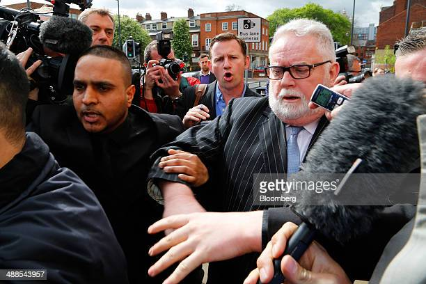 Paul Flowers former chairman of CoOperative Bank Plc right is surrounded by media as he leaves Leeds Magistrates Court in Leeds UK on Wednesday May 7...