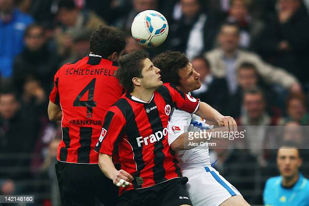 Paul Freier of Bochum jumps for a header with Pirmin Schwegler and Gordon Schildenfeld of Frankfurt during the Second Bundesliga match between...