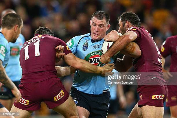 Paul Gallen of the Blues is tackled by Maroons captain Cameron Smith during game three of the State of Origin series between the Queensland Maroons...