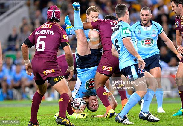 Paul Gallen of the Blues is upended in the tackle Sam Thaiday of the Maroons during game two of the State Of Origin series between the Queensland...