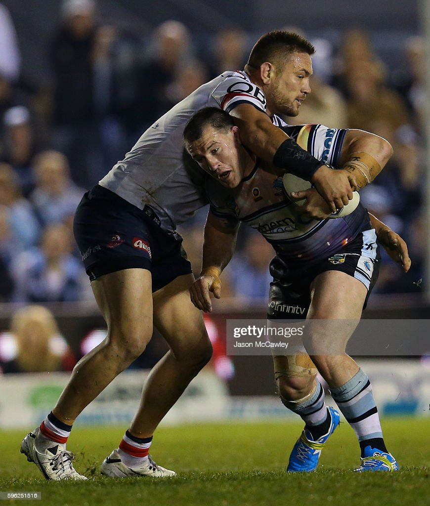 Paul Gallen of the Sharks is tackled by Jared Waerea-Hargreaves of the Roosters during the round 25 NRL match between the Cronulla Sharks and the Sydney Roosters at Shark Park on August 27, 2016 in Sydney, Australia.