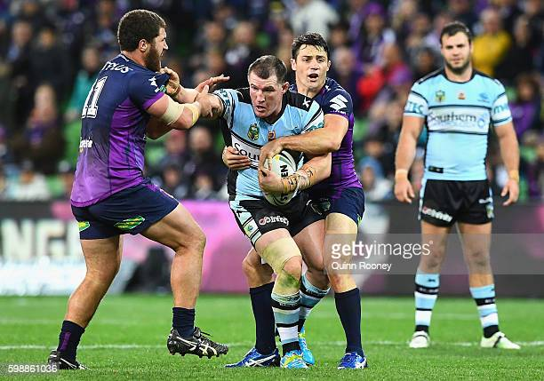 Paul Gallen of the Sharks is tackled by Kenny Bromwich and Cooper Cronk of the Stormduring the round 26 NRL match between the Melbourne Storm and the...