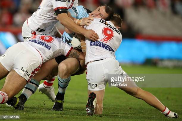 Paul Gallen of the Sharks is tackled by Paul Vaughan and Cameron McInnes of the Dragons during the round 10 NRL match between the St George Illawarra...