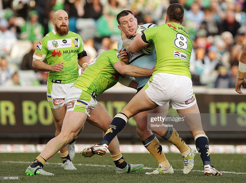 Paul Gallen of the Sharks is tackled during the round 19 NRL match between the Canberra Raiders and the Cronulla Sharks at GIO Stadium on July 18, 2015 in Canberra, Australia.