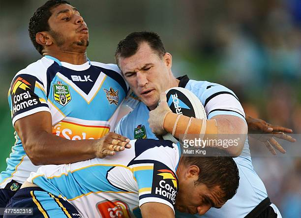 Paul Gallen of the Sharks is tackled during the round one NRL match between the Cronulla Sharks and the Gold Coast Titans at Remondis Stadium on...