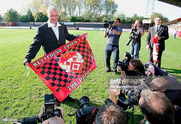 Paul Gascoigne poses with a team flag as he is announced as manager of Kettering Town as his consortium takes over the club after having an offer...