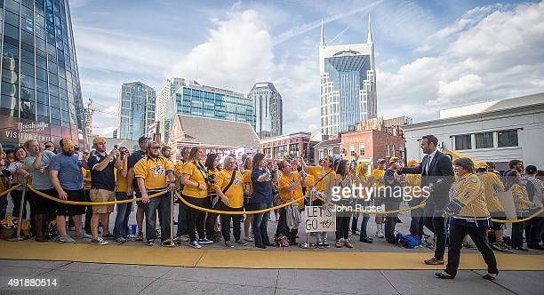 Paul Gaustad of the Nashville Predators greets fans along the 'Gold Walk' as he arrives to play an NHL game against the Carolina Hurricanes on...