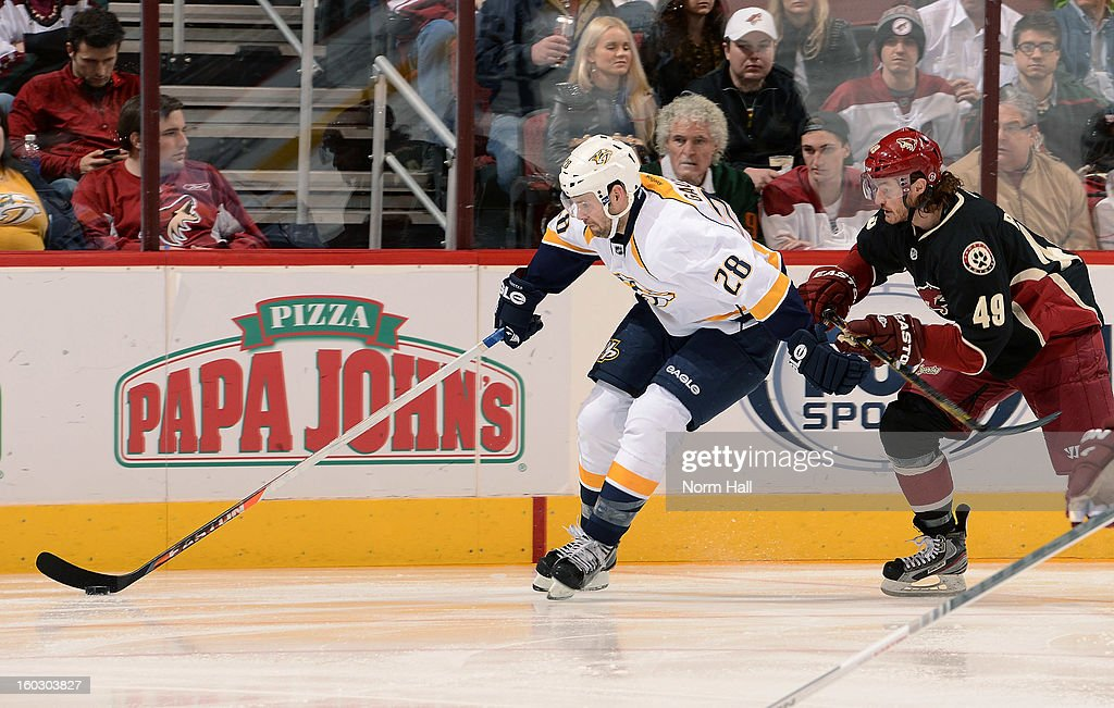 Paul Gaustad #28 of the Nashville Predators skates the puck up ice past Alexandre Bolduc #49 of the Phoenix Coyotes at Jobing.com Arena on January 28, 2013 in Glendale, Arizona.