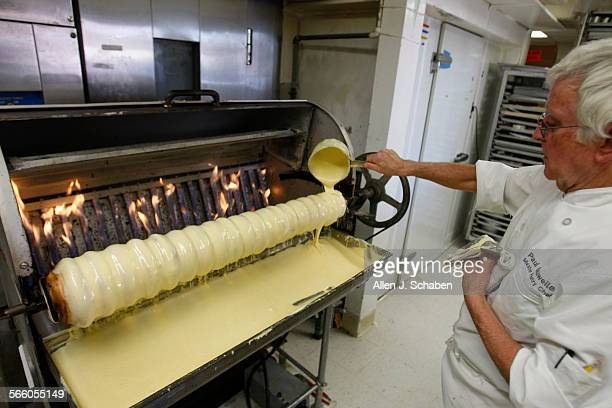Paul Gauweiler pours a special batter to make Baumkuchen cake in a Baumkuchen machine at The Cake Box in Huntington Beach The German bakers make...