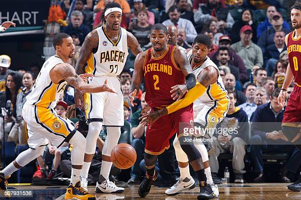 Paul George and George Hill of the Indiana Pacers defend against Kyrie Irving of the Cleveland Cavaliers in the first half of the game at Bankers...