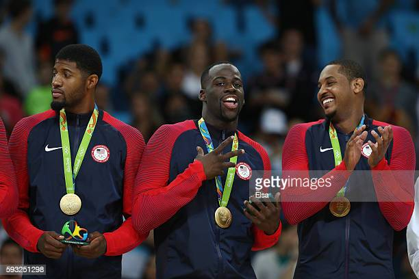 Paul George Draymond Green and Carmelo Anthony stand on the podium with gold medals after defeating Serbia during the Men's Gold medal game on Day 16...