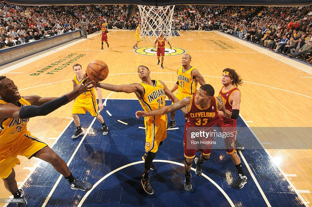 Paul George #24 of the Indiana Pacers and <a gi-track='captionPersonalityLinkClicked' href=/galleries/search?phrase=Ian+Mahinmi&family=editorial&specificpeople=740196 ng-click='$event.stopPropagation()'>Ian Mahinmi</a> #28 of the Indiana Pacers pass the ball during the game between the Indiana Pacers and the Cleveland Cavaliers on December 12, 2012 at Bankers Life Fieldhouse in Indianapolis, Indiana.