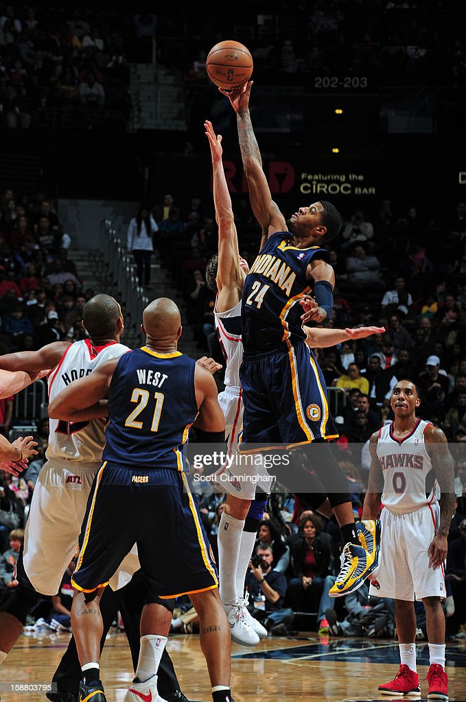 Paul George #24 of the Indiana Pacers battles for a jump ball against Kyle Korver #26 of the Atlanta Hawks on December 29, 2012 at Philips Arena in Atlanta, Georgia.