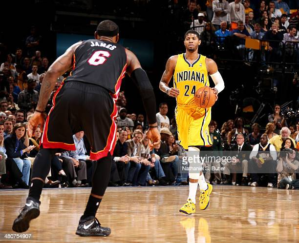 Paul George of the Indiana Pacers brings the ball up court against LeBron James of the Miami Heat during a game on March 26 2014 at Bankers Life...
