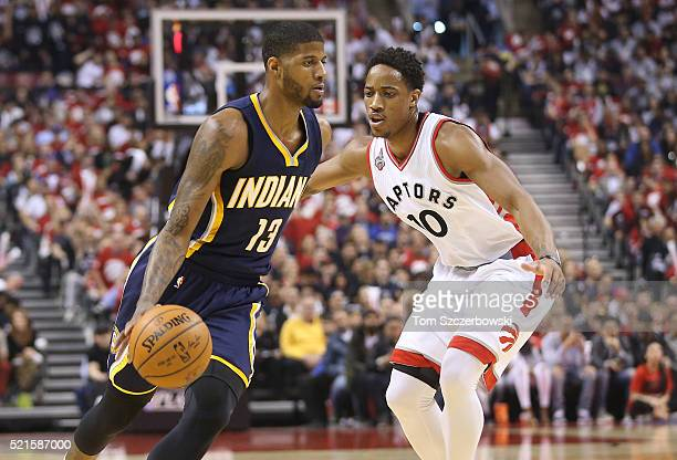 Paul George of the Indiana Pacers dribbles against DeMar DeRozan of the Toronto Raptors in Game One of the Eastern Conference Quarterfinals during...