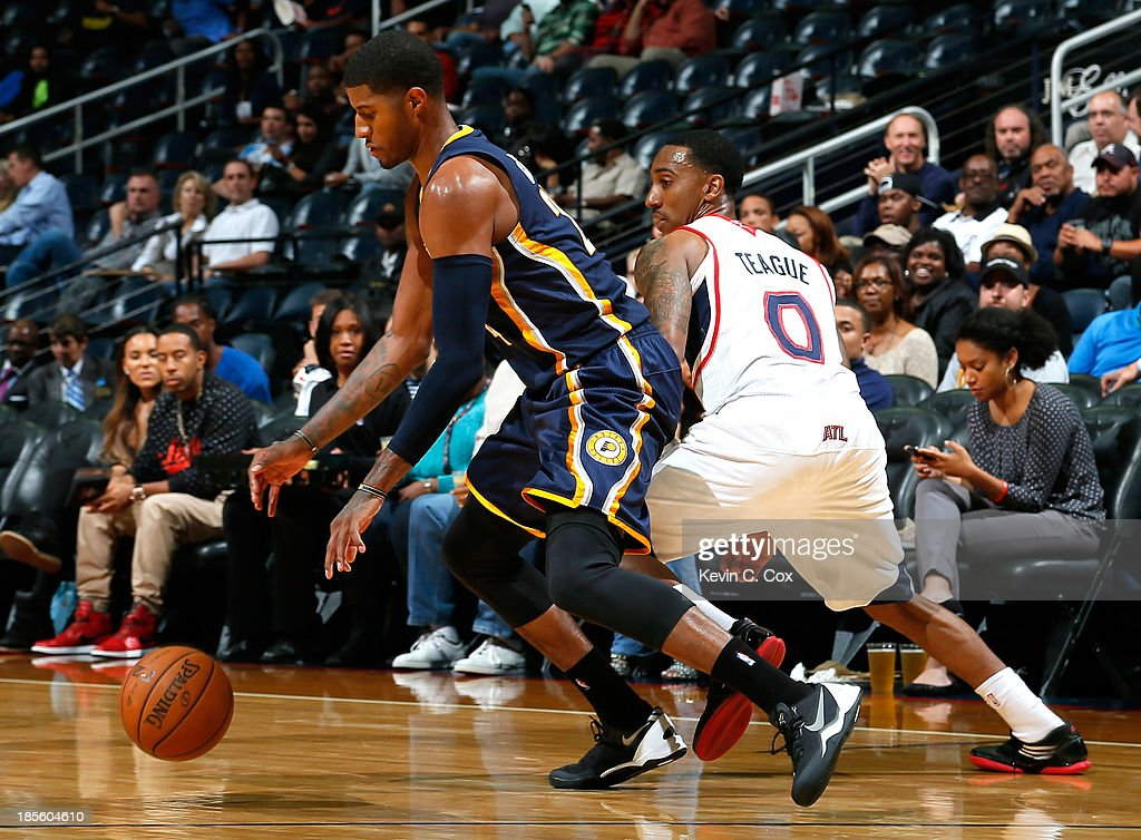 Paul George #24 of the Indiana Pacers dribbles away from Jeff Teague #0 of the Atlanta Hawks at Philips Arena on October 22, 2013 in Atlanta, Georgia.