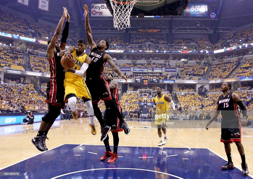 Paul George #24 of the Indiana Pacers drives to the basket against Chris Bosh #1 and Udonis Haslem #40 of the Miami Heat during Game Two of the Eastern Conference Finals of the 2014 NBA Playoffs at at Bankers Life Fieldhouse on May 20, 2014 in Indianapolis, Indiana.