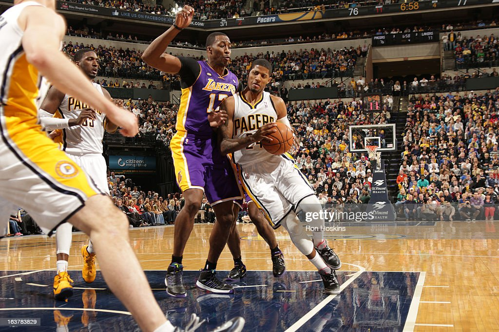 Paul George #24 of the Indiana Pacers drives to the basket against Dwight Howard #12 of the Los Angeles Lakers on March 15, 2013 at Bankers Life Fieldhouse in Indianapolis, Indiana.