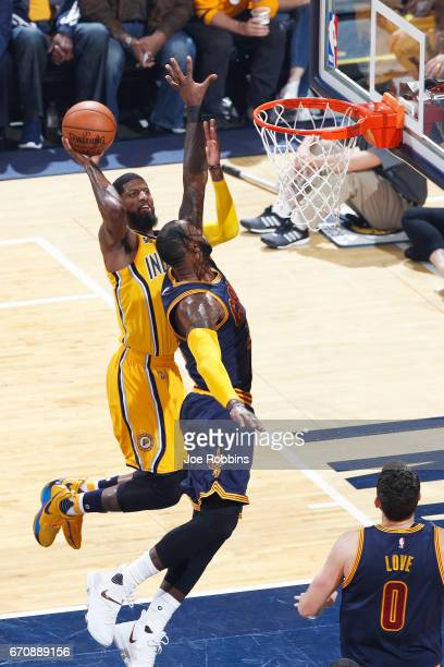Paul George of the Indiana Pacers drives to the basket while defended by LeBron James of the Cleveland Cavaliers in the first quarter of game three...