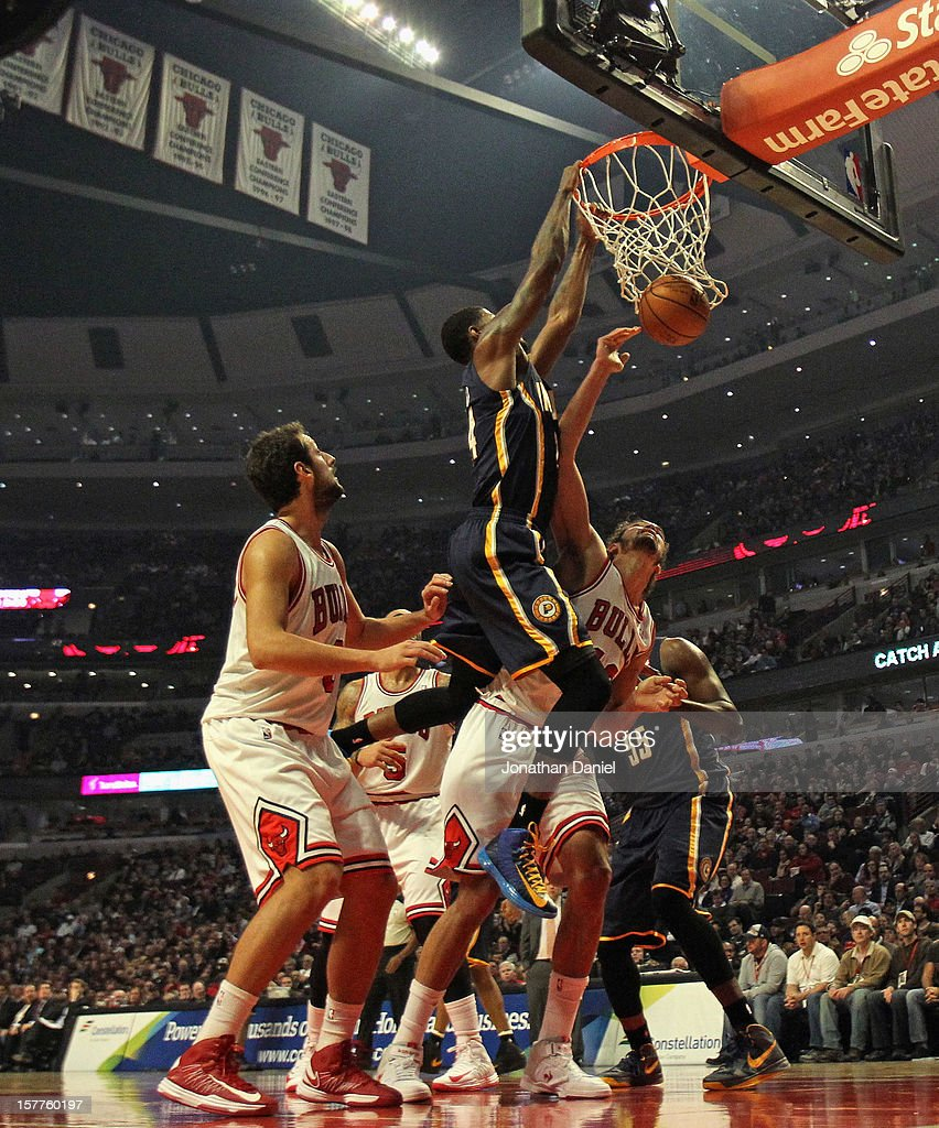 Paul George #24 of the Indiana Pacers dunks over <a gi-track='captionPersonalityLinkClicked' href=/galleries/search?phrase=Joakim+Noah&family=editorial&specificpeople=699038 ng-click='$event.stopPropagation()'>Joakim Noah</a> #13 and <a gi-track='captionPersonalityLinkClicked' href=/galleries/search?phrase=Marco+Belinelli&family=editorial&specificpeople=847592 ng-click='$event.stopPropagation()'>Marco Belinelli</a> #8 of the Chicago Bulls at the United Center on December 4, 2012 in Chicago, Illinois.
