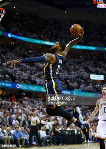 Paul George of the Indiana Pacers goes in for a first half dunk in front of Kevin Love of the Cleveland Cavaliers in Game Two of the Eastern...