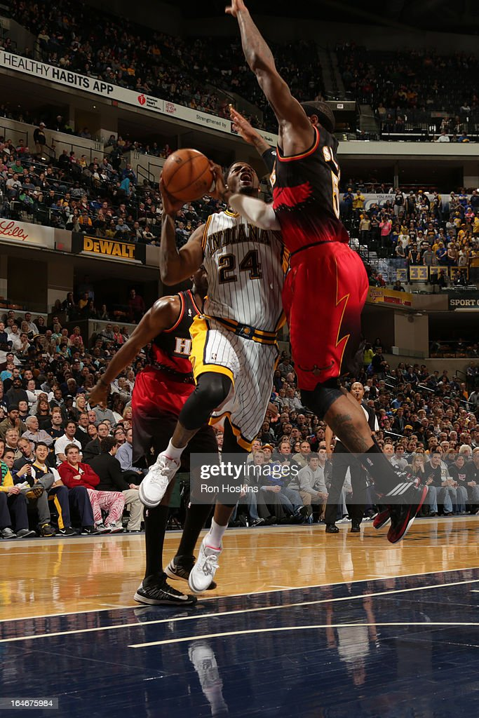 Paul George #24 of the Indiana Pacers goes to the basket against <a gi-track='captionPersonalityLinkClicked' href=/galleries/search?phrase=Josh+Smith+-+Basketball+Player+-+Born+1985&family=editorial&specificpeople=201983 ng-click='$event.stopPropagation()'>Josh Smith</a> #5 of the Atlanta Hawks on March 25, 2013 at Bankers Life Fieldhouse in Indianapolis, Indiana.