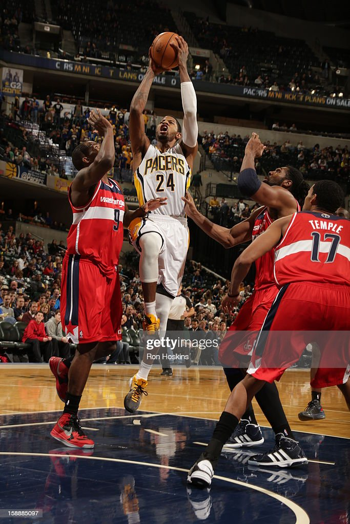 Paul George #24 of the Indiana Pacers goes to the basket against <a gi-track='captionPersonalityLinkClicked' href=/galleries/search?phrase=Martell+Webster&family=editorial&specificpeople=601785 ng-click='$event.stopPropagation()'>Martell Webster</a> #9 and Nene #42 and <a gi-track='captionPersonalityLinkClicked' href=/galleries/search?phrase=Garrett+Temple&family=editorial&specificpeople=709398 ng-click='$event.stopPropagation()'>Garrett Temple</a> #17 of the Washington Wizards on January 2, 2013 at Bankers Life Fieldhouse in Indianapolis, Indiana.