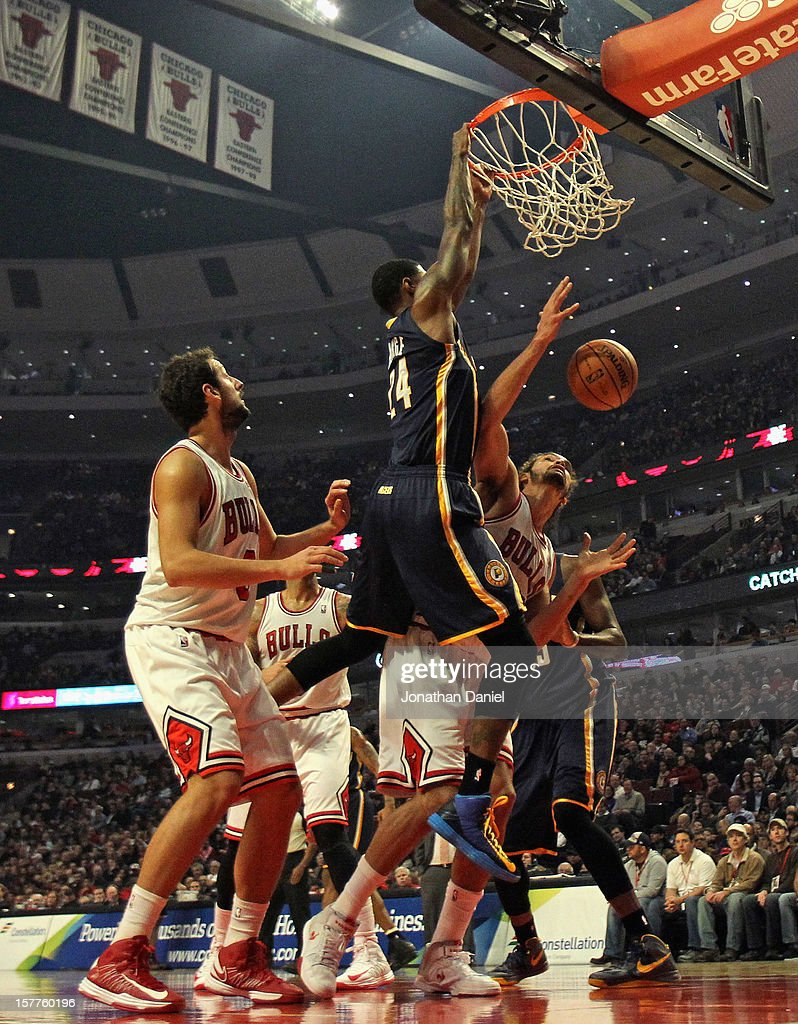 Paul George #24 of the Indiana Pacers goes up for a dunk over <a gi-track='captionPersonalityLinkClicked' href=/galleries/search?phrase=Joakim+Noah&family=editorial&specificpeople=699038 ng-click='$event.stopPropagation()'>Joakim Noah</a> #13 and <a gi-track='captionPersonalityLinkClicked' href=/galleries/search?phrase=Marco+Belinelli&family=editorial&specificpeople=847592 ng-click='$event.stopPropagation()'>Marco Belinelli</a> #8 of the Chicago Bulls at the United Center on December 4, 2012 in Chicago, Illinois.
