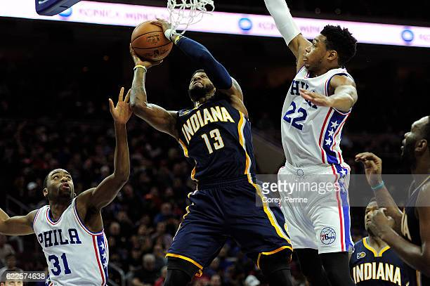 Paul George of the Indiana Pacers is guarded at the rim by Hollis Thompson and Richaun Holmes of the Philadelphia 76ers in the third quarter at the...