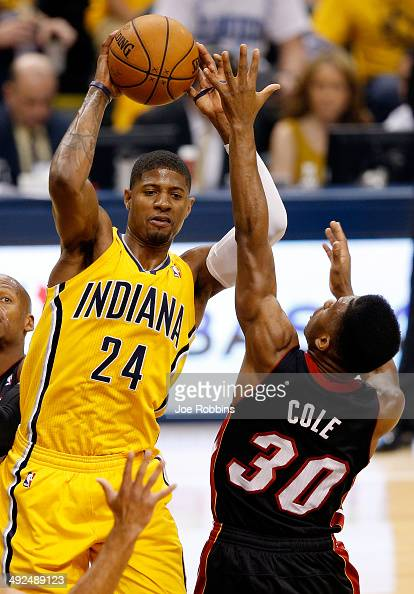 Paul George of the Indiana Pacers looks to pass as Norris Cole of the Miami Heat defends during Game Two of the Eastern Conference Finals of the 2014...