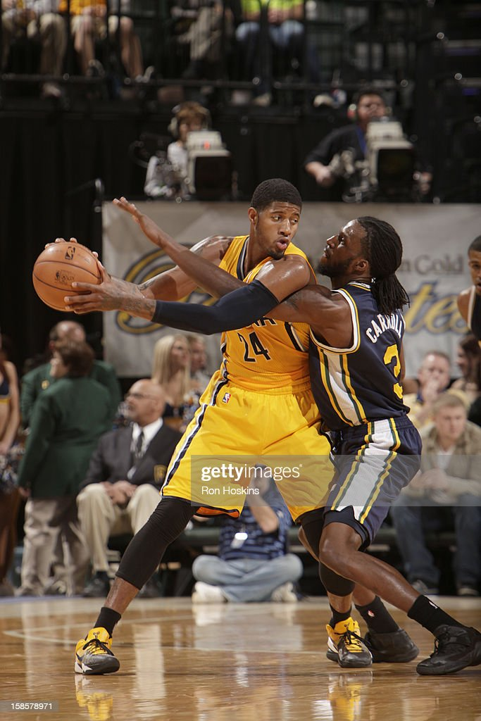 Paul George #24 of the Indiana Pacers protects the ball from <a gi-track='captionPersonalityLinkClicked' href=/galleries/search?phrase=DeMarre+Carroll&family=editorial&specificpeople=784686 ng-click='$event.stopPropagation()'>DeMarre Carroll</a> #3 of the Utah Jazz during the game between the Indiana Pacers and the Utah Jazz on December 19, 2012 at Bankers Life Fieldhouse in Indianapolis, Indiana.