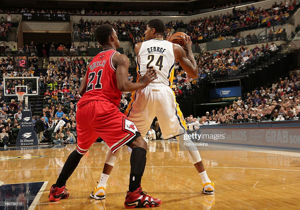 Paul George #24 of the Indiana Pacers protects the ball from <a gi-track='captionPersonalityLinkClicked' href=/galleries/search?phrase=Jimmy+Butler+-+Jugador+de+baloncesto&family=editorial&specificpeople=9860567 ng-click='$event.stopPropagation()'>Jimmy Butler</a> #21 of the Chicago Bulls during the game between the Indiana Pacers and the Chicago Bulls on February 4, 2013 at Bankers Life Fieldhouse in Indianapolis, Indiana.