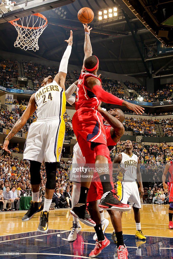 Paul George #24 of the Indiana Pacers reaches for a rebound against Josh Smith #5 of the Atlanta Hawks in Game Five of the Eastern Conference Quarterfinals during the 2013 NBA Playoffs on May 1, 2013 at Bankers Life Fieldhouse in Indianapolis, Indiana.