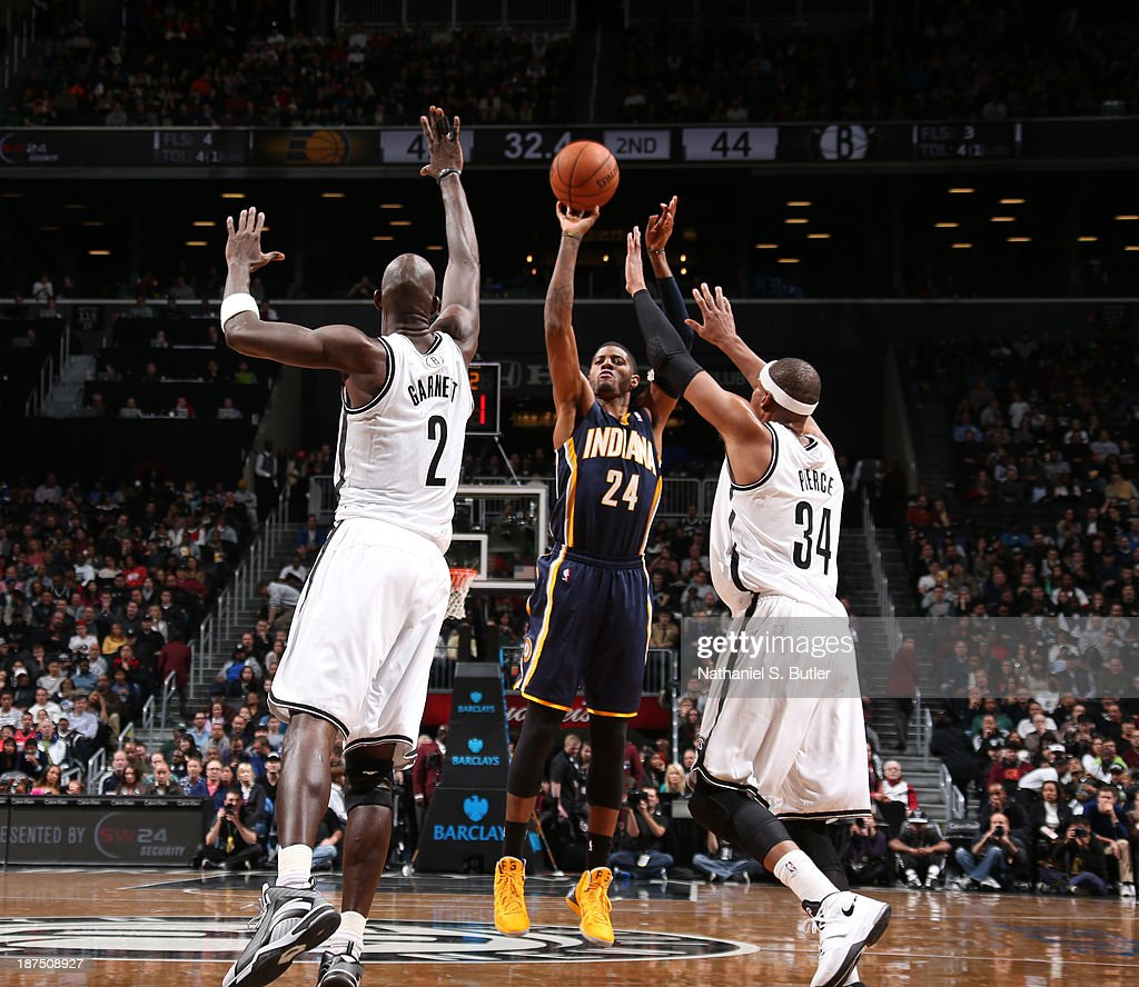Paul George #24 of the Indiana Pacers shoots against Kevin Garnett #2 of the Brooklyn Nets and Paul Pierce #34 of the Brooklyn Nets during a game at Barclays Center on November 9, 2013 in the Brooklyn borough of New York City.
