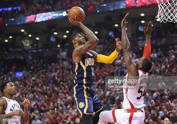 Paul George of the Indiana Pacers shoots against Patrick Patterson of the Toronto Raptors in Game One of the Eastern Conference Quarterfinals during...