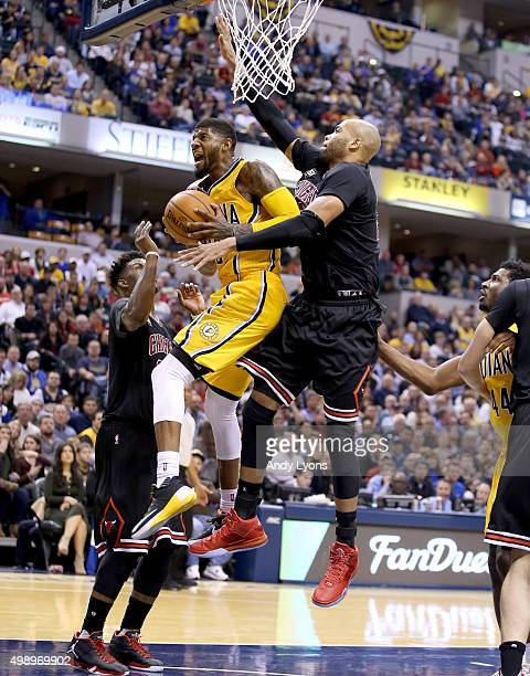 Paul George of the Indiana Pacers shoots the ball while defended by Taj Gibson of the Chicago Bulls at Bankers Life Fieldhouse on November 27 2015 in...