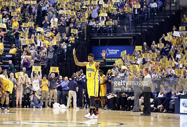 Paul George of the Indiana Pacers waves to the crowd as he walks onto the court for the first time in the game against the Miami Heat at Bankers Life...