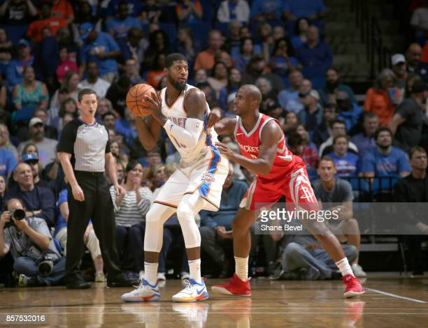 Paul George of the Okahoma City Thunder posts up against Chris Paul of the Houston Rockets during the preseason game on October 3 2017 at the BOK...
