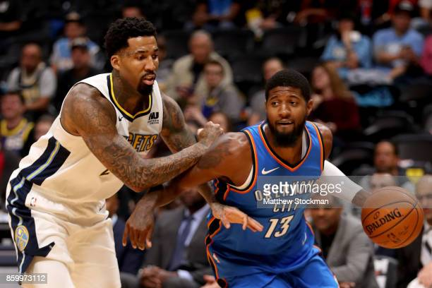 Paul George of the Oklahoma City Thunder drives to the basket against Wilson Chandler of the Denver Nuggets at the Pepsi Center on October 10 2017 in...