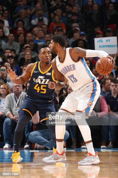 Paul George of the Oklahoma City Thunder handles the ball against Donovan Mitchell of the Utah Jazz on December 5 2017 at Chesapeake Energy Arena in...