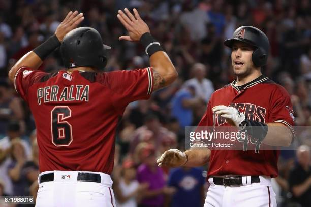 Paul Goldschmidt of the Arizona Diamondbacks high fives David Peralta after Goldschmidt hit a two run home run against the Los Angeles Dodgers during...