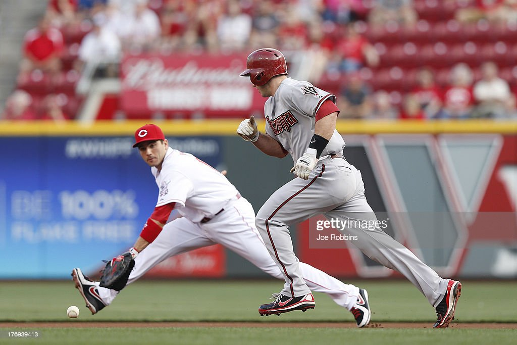 <a gi-track='captionPersonalityLinkClicked' href=/galleries/search?phrase=Paul+Goldschmidt&family=editorial&specificpeople=7511120 ng-click='$event.stopPropagation()'>Paul Goldschmidt</a> #44 of the Arizona Diamondbacks avoids the ball before being fielded by <a gi-track='captionPersonalityLinkClicked' href=/galleries/search?phrase=Joey+Votto&family=editorial&specificpeople=759319 ng-click='$event.stopPropagation()'>Joey Votto</a> #19 of the Cincinnati Reds during the game at Great American Ball Park on August 19, 2013 in Cincinnati, Ohio.