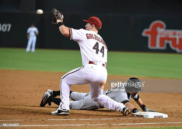 Paul Goldschmidt of the Arizona Diamondbacks catches a throw from the pitcher as Ichiro Suzuki of the Miami Marlins dives back to first base during...
